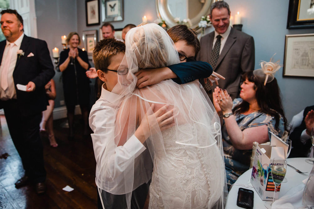 brides sons share intimate moment with bride with a double hug