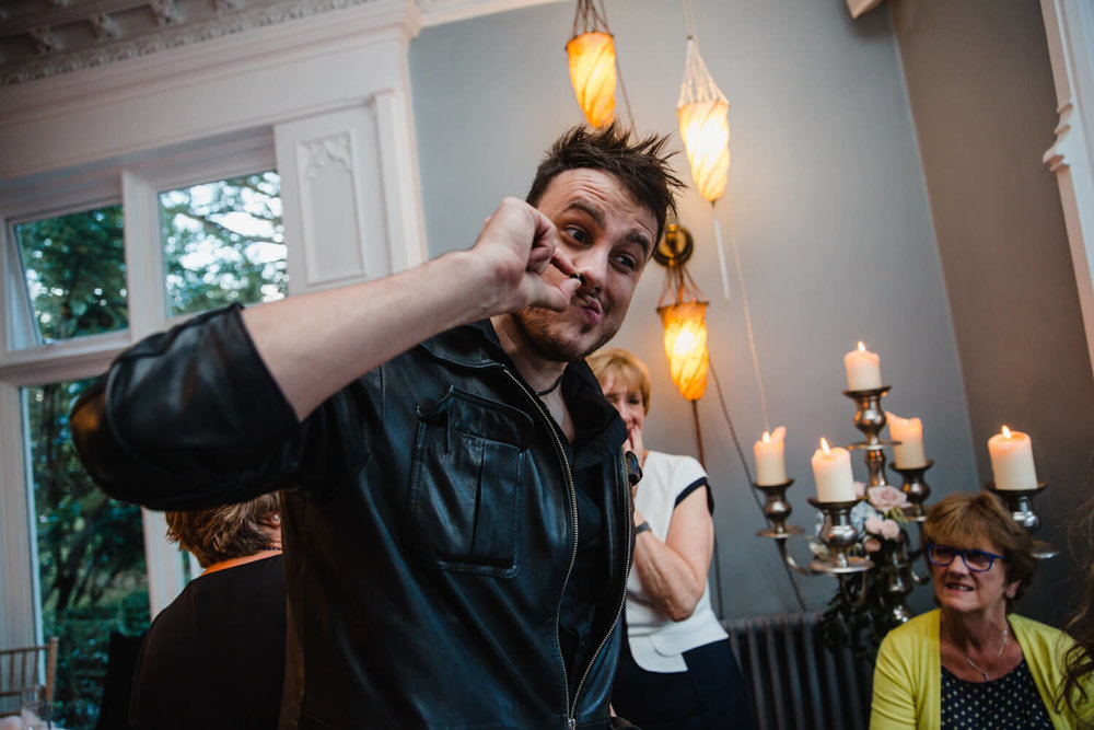 magician working nail all the way up nose to bewilderment of guests