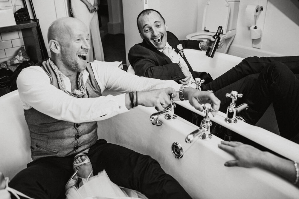 groom and friend sat in didsbury house hotel double bath tub playing with taps
