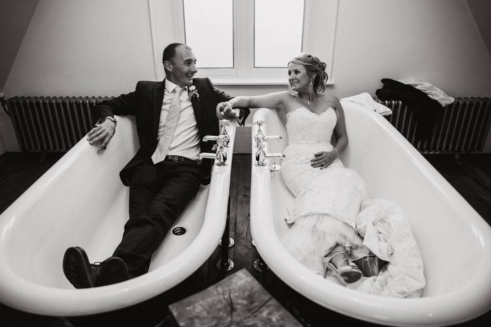 bride and groom lay down for a portrait in the double bathtub at didsbury house hotel