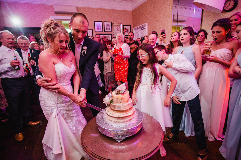 newlyweds cut their wedding cake in front of friends and family at didsbury house hotel
