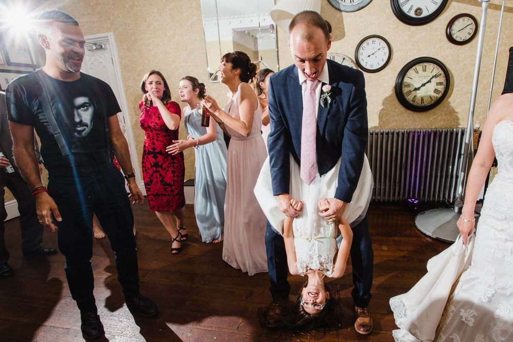 groom holding flower girl upside down on dance floor