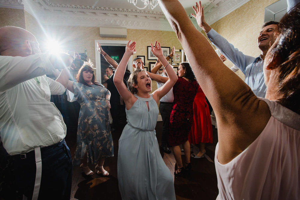 bridesmaids and wedding guests all partying on dance floor with arms in the air