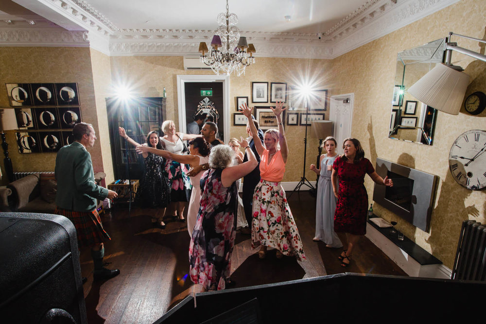 wide angle photograph of wedding party dancing to floorfillas DJ set