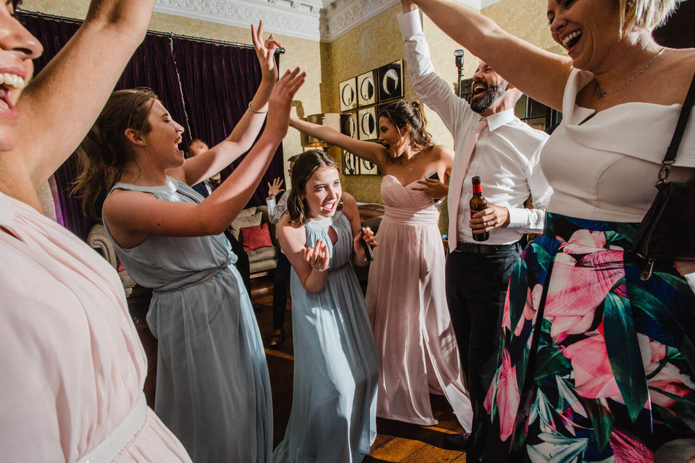 bridesmaids all together with arms in air dancing to music