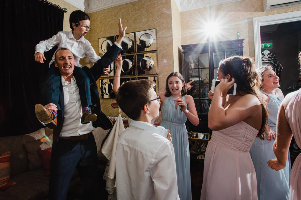 groom with boy on his shoulders dancing to DJ music while guests party around them