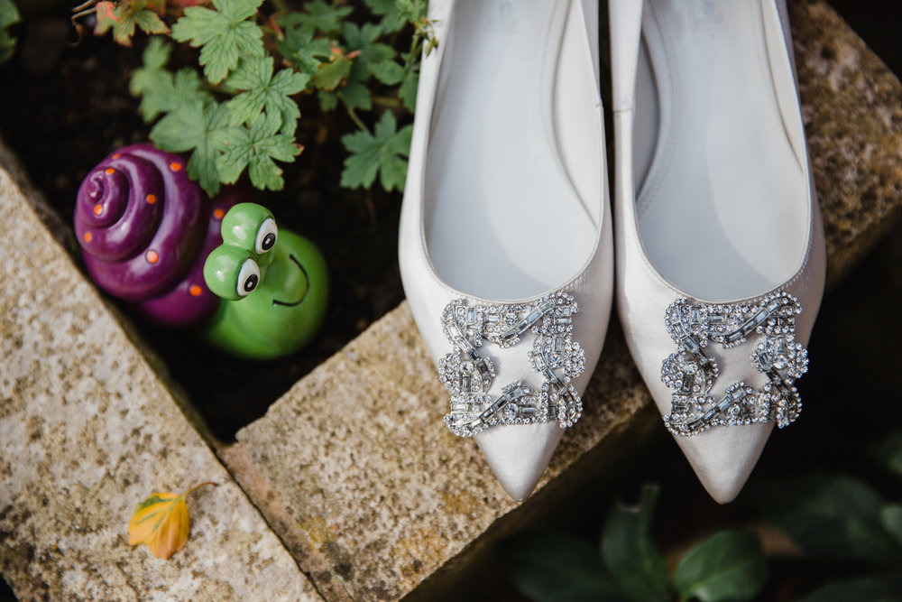close up of wedding shoes in a flower pot next to pottery snail