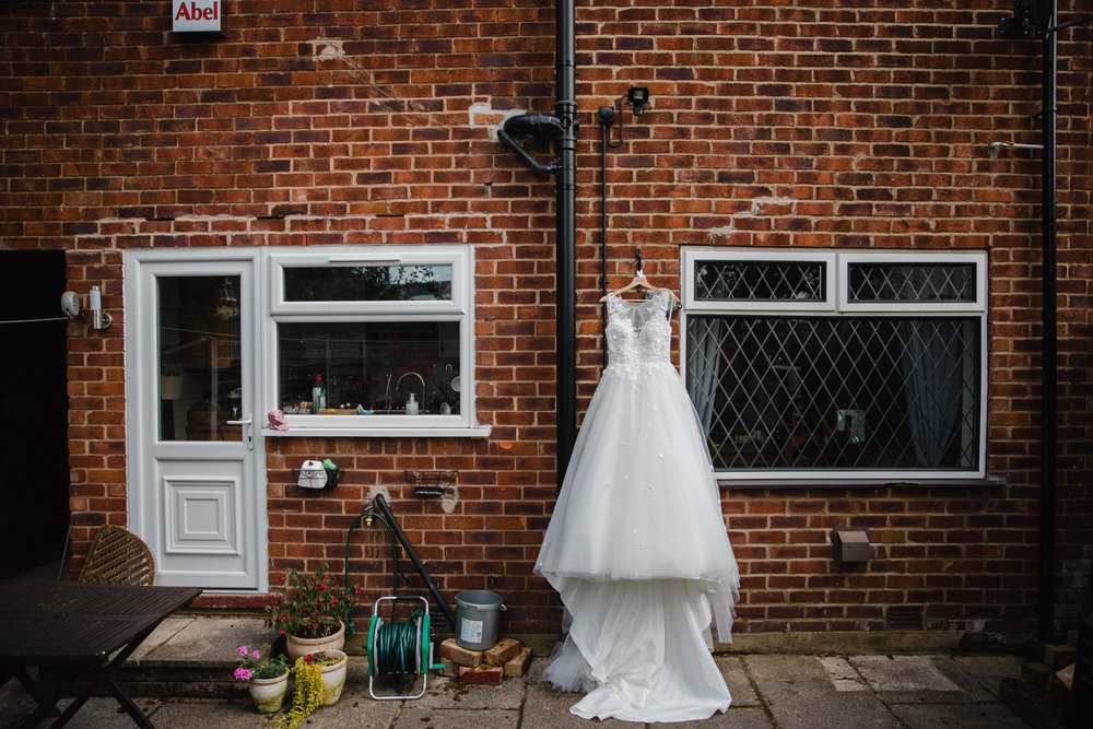 wedding dress hung on wall in back garden of house