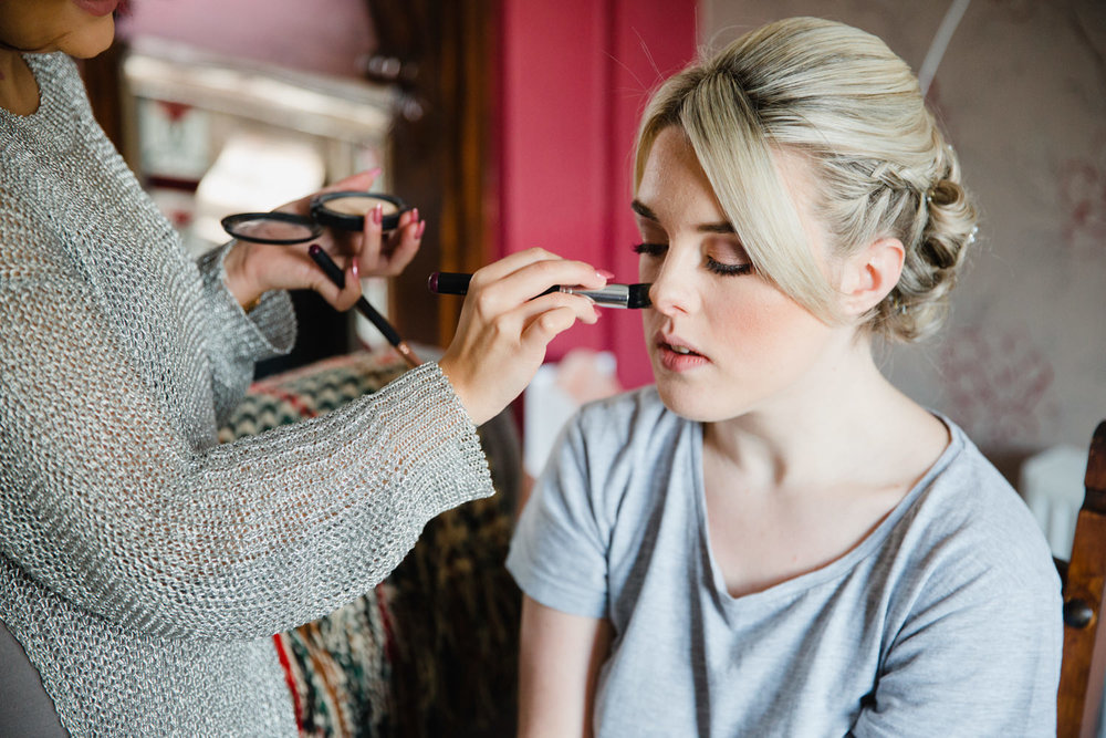 bridesmaid receiving make up sat in living room