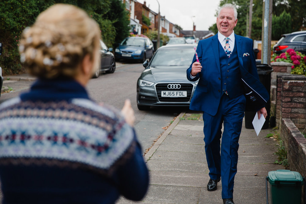 father of the bride walking down the road arriving with a toothbrush for bridesmaid