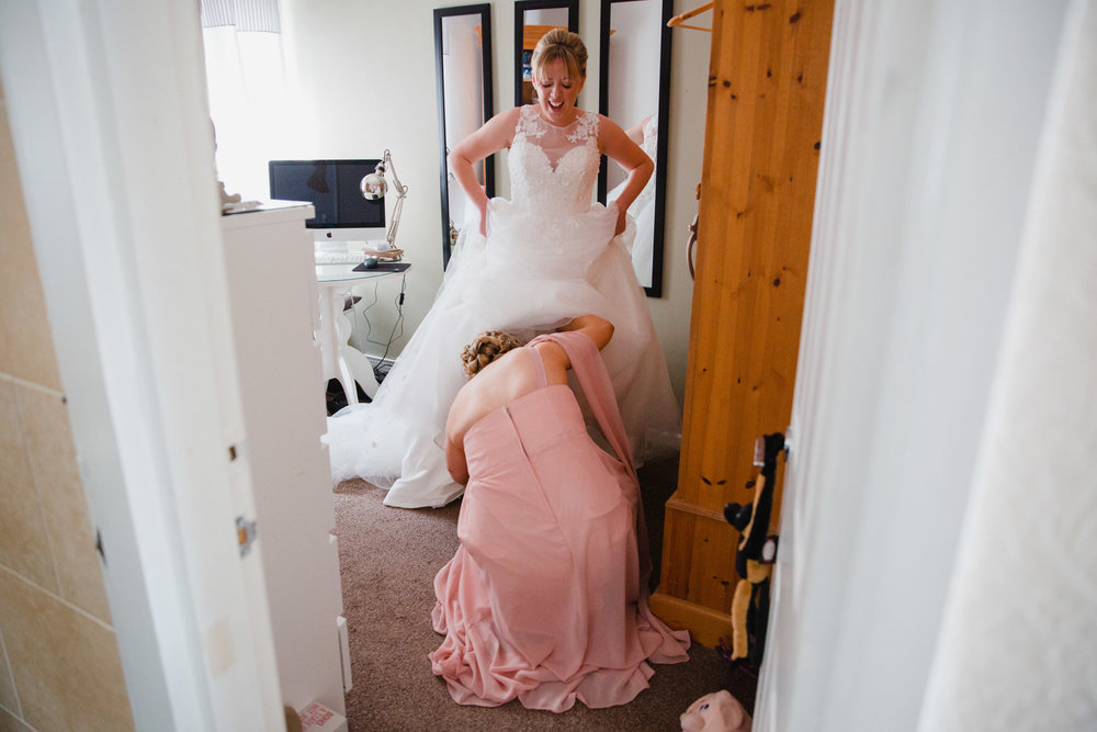 bridesmaid fitting shoes to bride under her dress while bride stands laughing