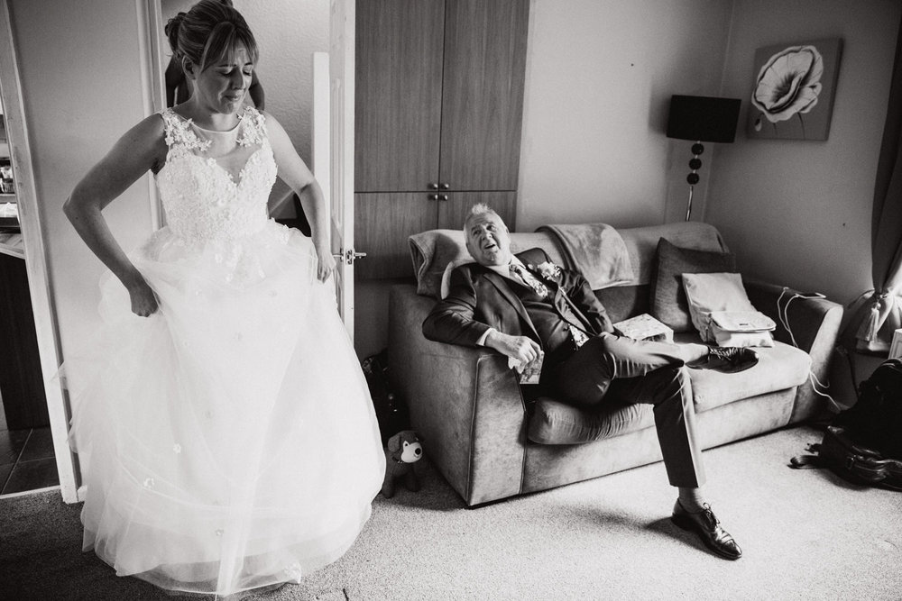 black and white photograph of bride coming down the stairs to be greeted by her father in living room