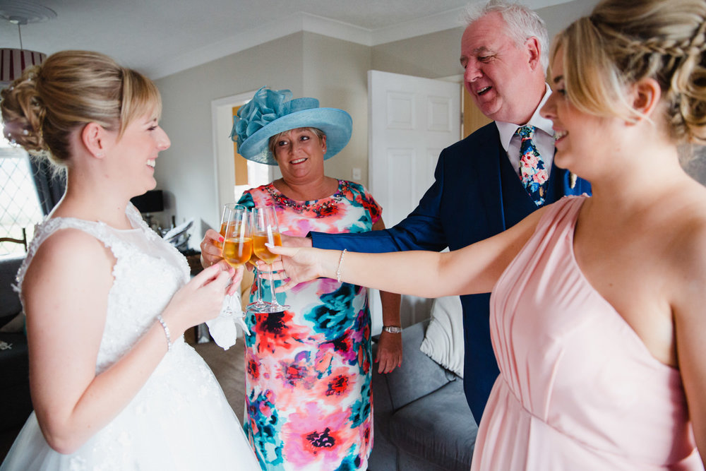 bride and family clinking champagne flutes together in celebration for wedding