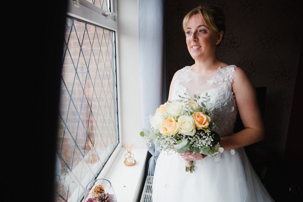 bride holding bouquet of flowers while looking out of dining room window
