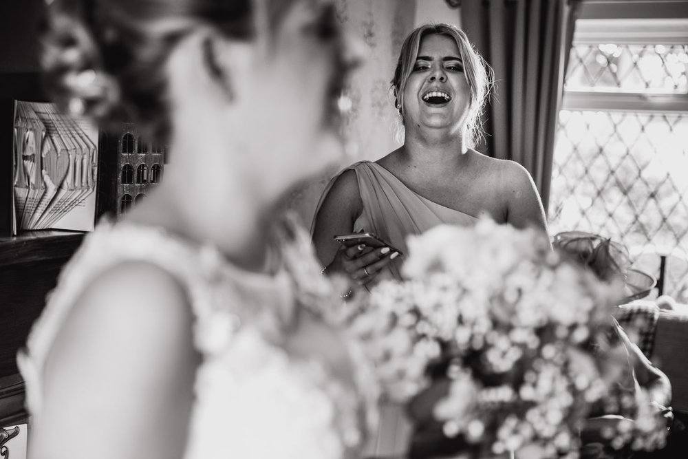 black and white photograph of sister of bride and bridesmaid laughing at bride while holding bouquets