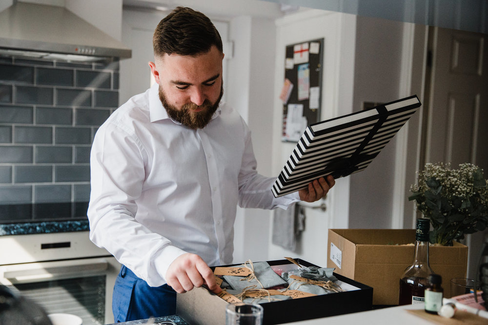 groom opening up large box of wedding gifts in the kitchen