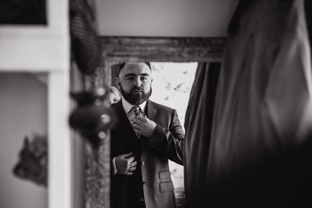 black and white photograph of groom in bedroom adjusting tie in mirror