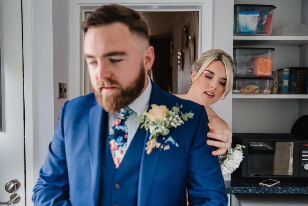 bridesmaid adjusting grooms suit jacket