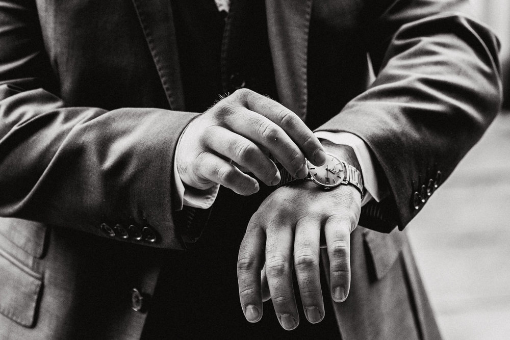 black and white photograph of groom adjusting his wedding present watch