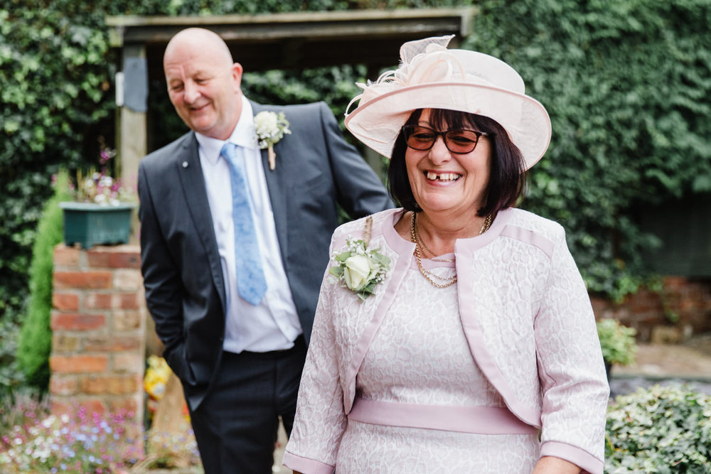 mother and father of groom outside in garden laughing together