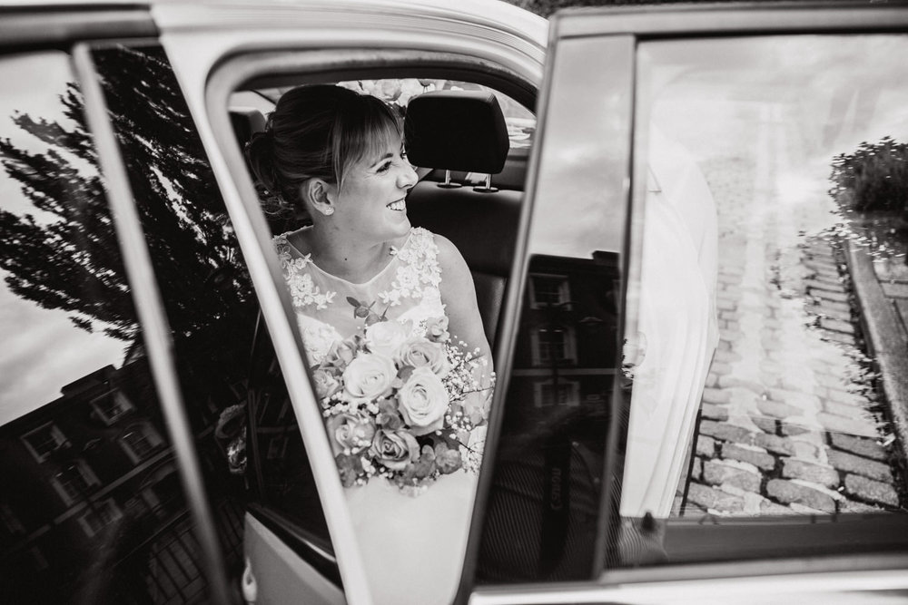black and white photograph of bride arriving in wedding car with a big smile while she holds her bouquet of flowers