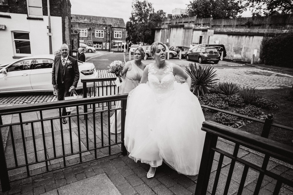 Bride with sister and father walking up the path to Stockport Town Hall wedding ceremony