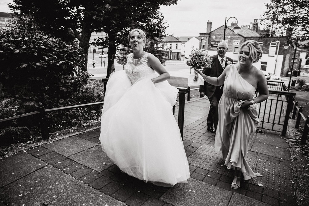 Bridal party laughing together while walking up the path to the stockport town hall wedding ceremony