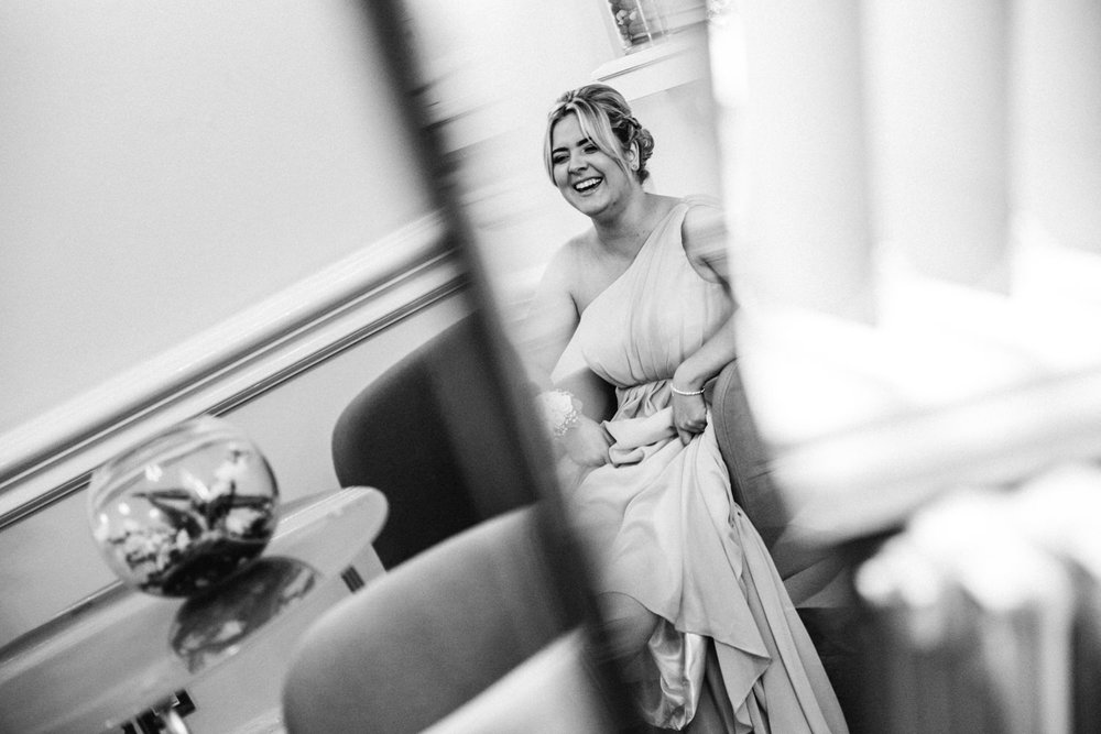 photograph in the mirror of bridesmaid sat in reception room