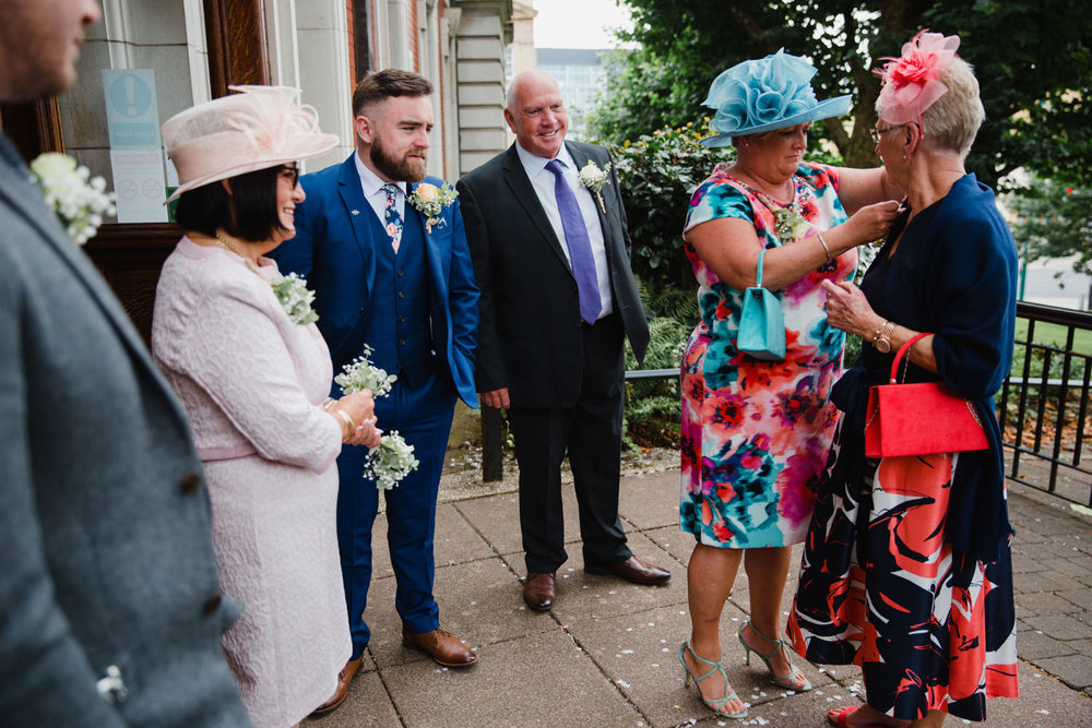 bridal party and guests outside attaching pinhole flowers to lapels and suit jackets