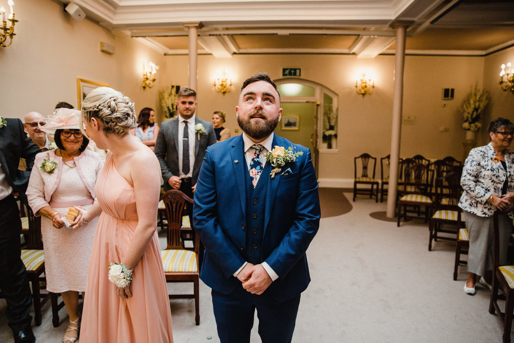groom looking nervous at the top of the aisle before wedding ceremony begins