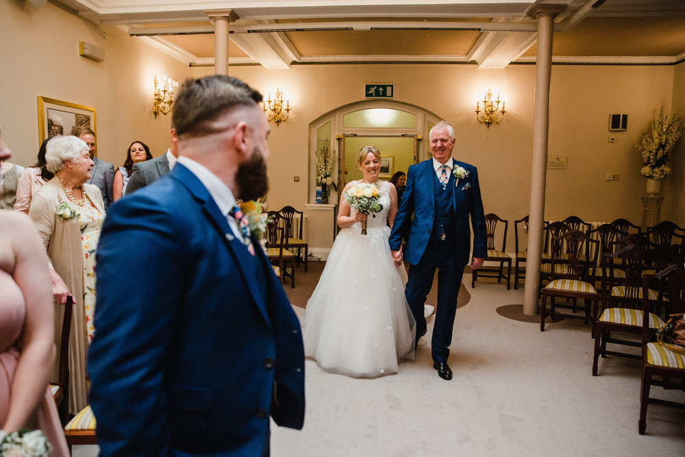 bride linking arms with her father as both are introduced into wedding ceremony room at stockport town hall