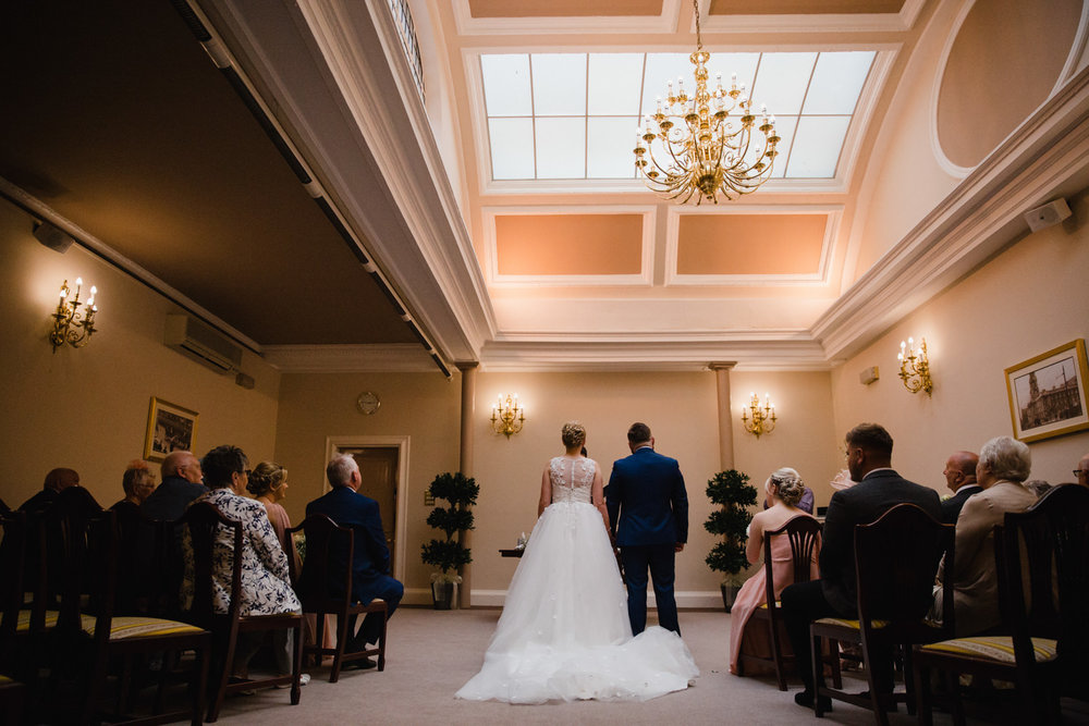 photograph taken from behind the ceremony of bride and groom holding hands while talking to registrar at stockport town hall