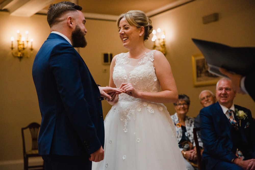 bride and groom exchange wedding rings in ceremony at stockport town hall