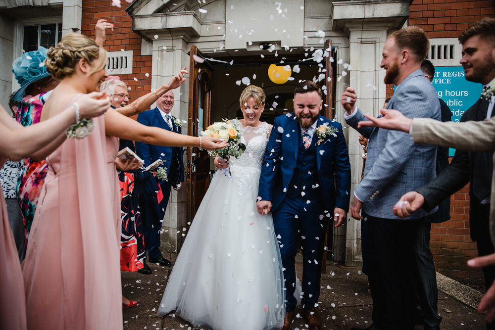 wedding party throwing confetti over bride and groom at Stockport Town Hall