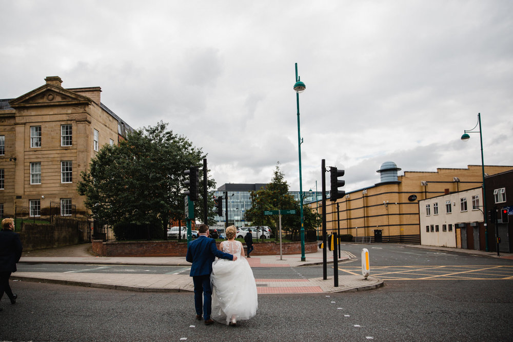 bride and groom crossing stockport road. Groom with arm around bride as both walk away from the camera
