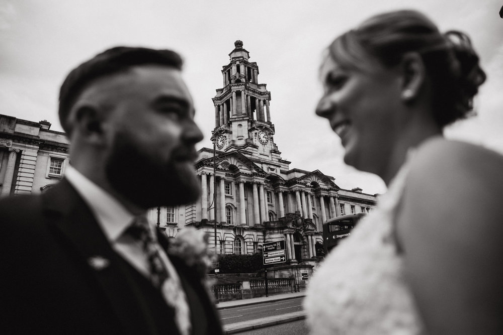 black and white portrait of bride and groom with stockport town hall spire in focus for the background and married couple blurred out in the foreground