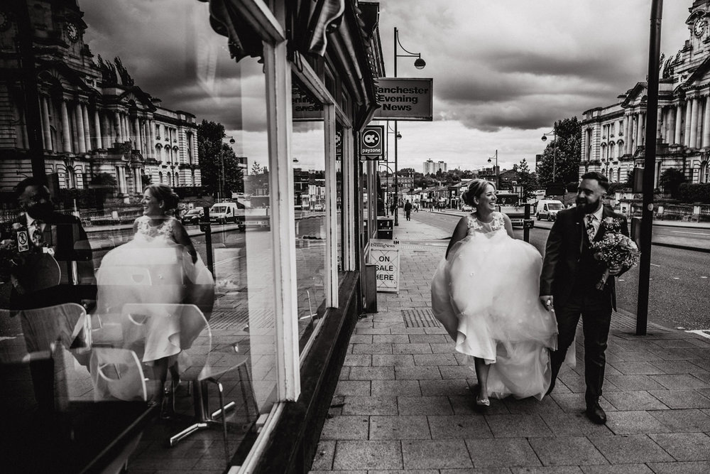 black and white photograph of bride and groom walking down stockport road with their reflection in shop window