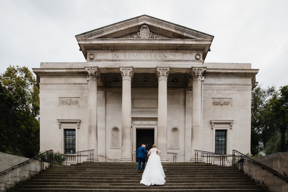 groom helping bride slowly climb steps of stockport art gallery