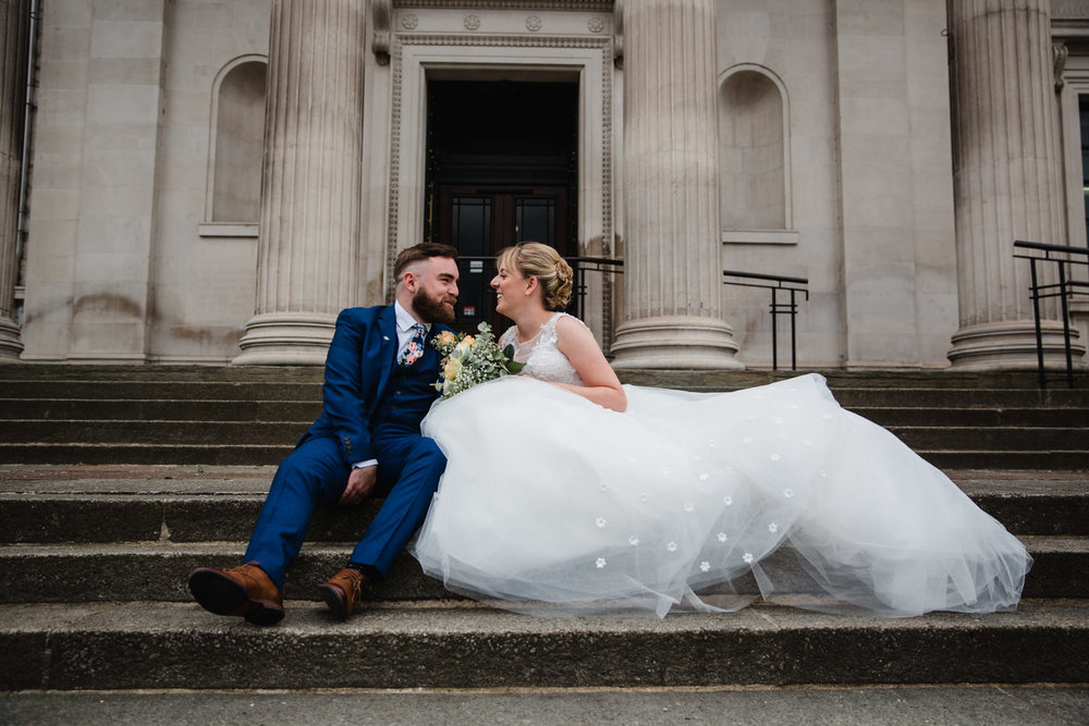 newlyweds sat on steps of stockport art galley