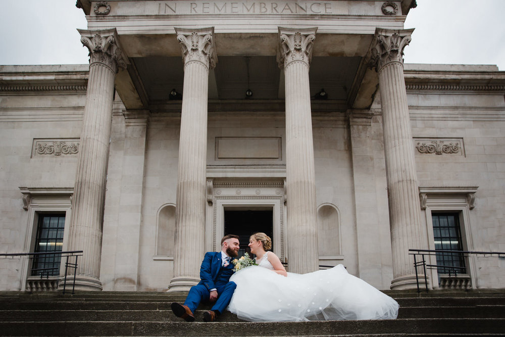 wide angle photograph of bride and groom on steps of stockport art gallery after their town hall ceremony