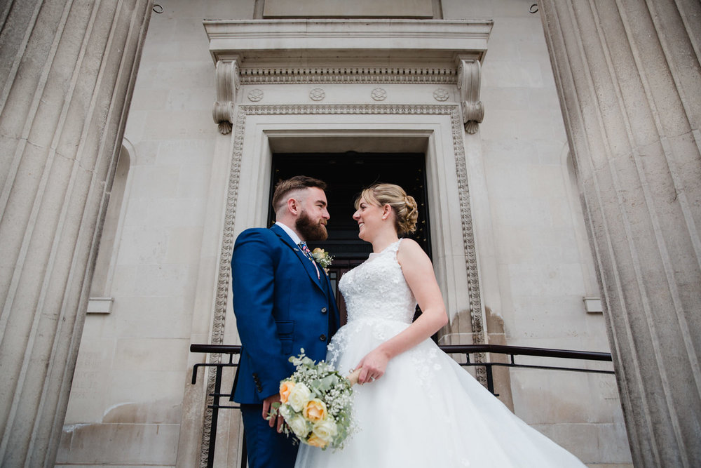 close up of married couple in front entrance of stockport art gallery