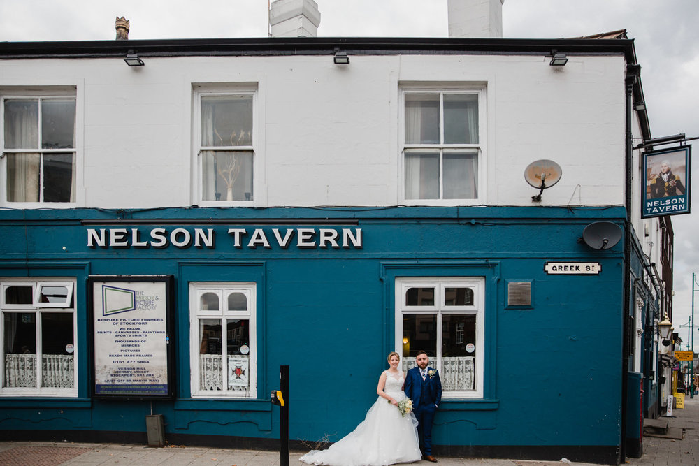 bride and groom in front of The Nelson Tavern blue wall. Bride holding bouquet while they both look straight at camera