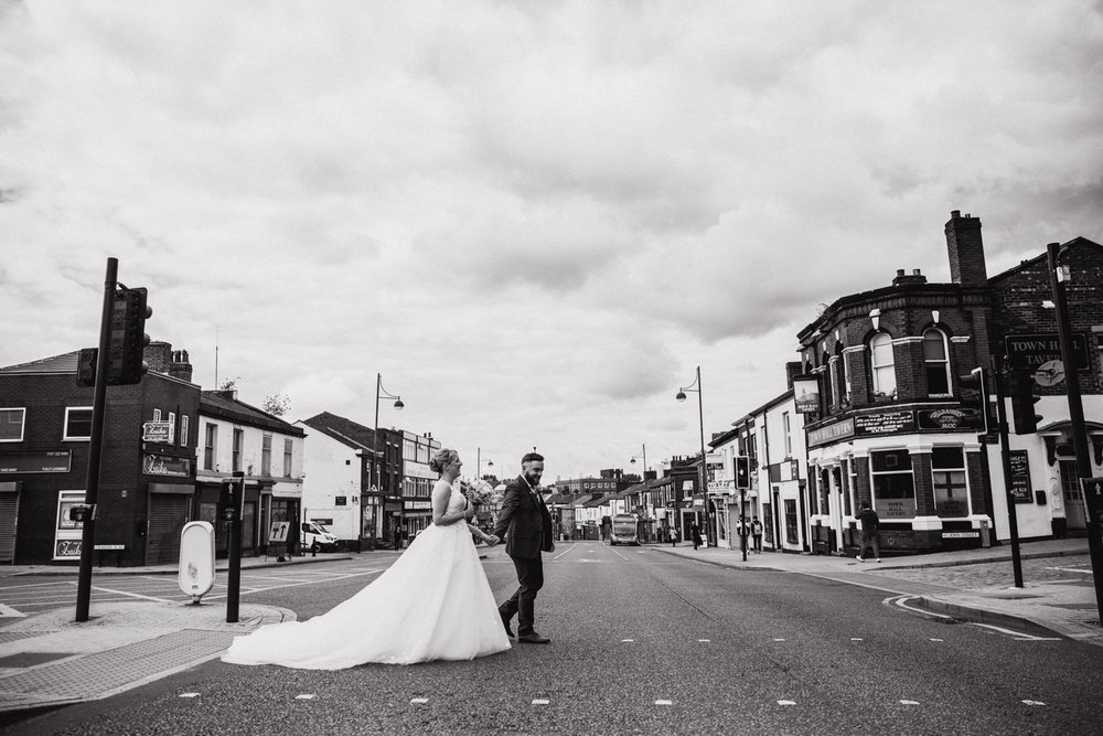 black and white photograph of bride and groom both crossing stockport road after their town hall wedding ceremony