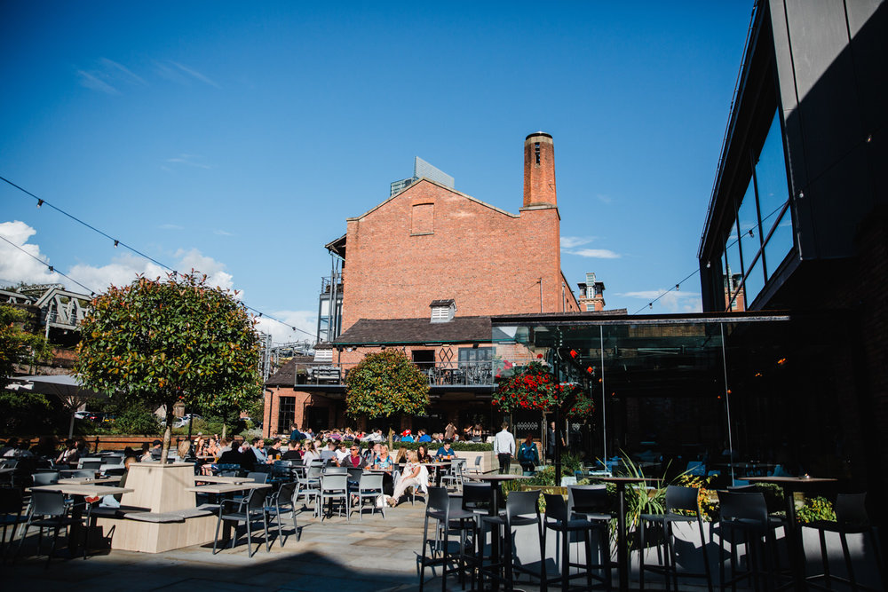 Castlefield Rooms wedding venue on a sunny day with blue skies and guests sat outside drinking