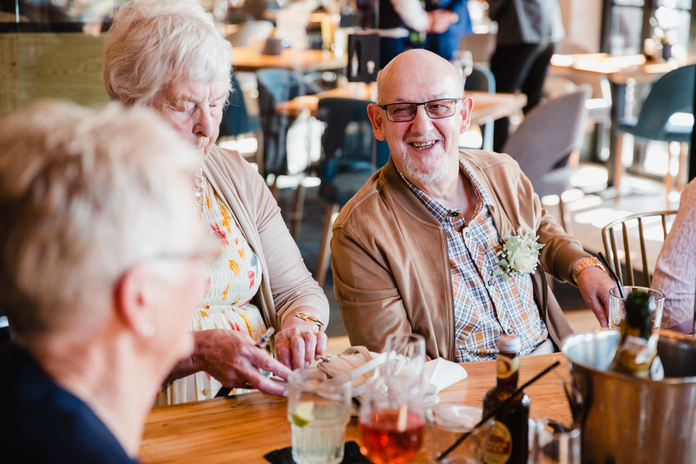 uncle wedding guest laughing with grandma sat at table