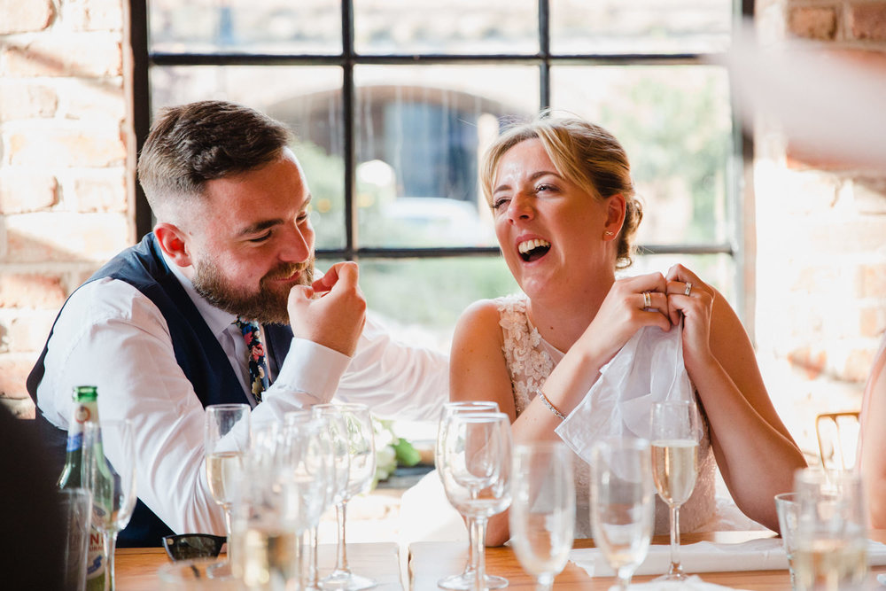 bride and groom sat at top table of reception laughing to speeches at The Castlefield Rooms