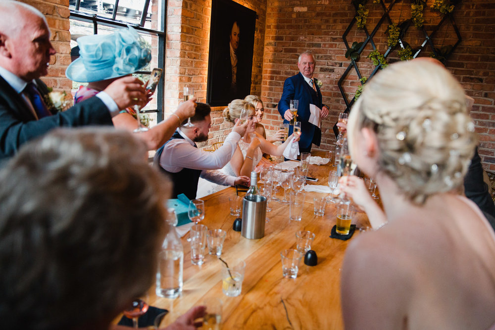 wedding party around the table raising a glass to bride and groom together