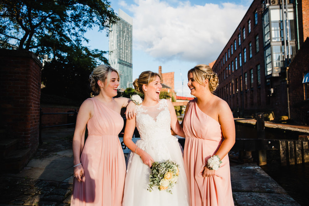 bride holding bouquet with bridesmaids at the castlefield rooms locks with beetham tower in the background