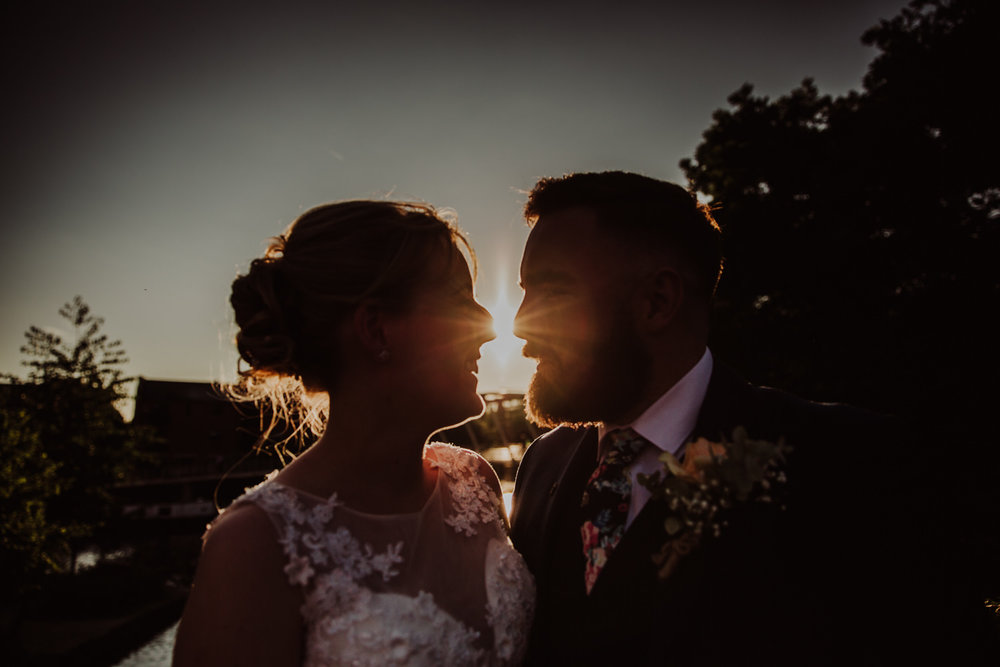 close up silhouette portrait photograph of the bride and groom together and the sun flare coming through between the two of them