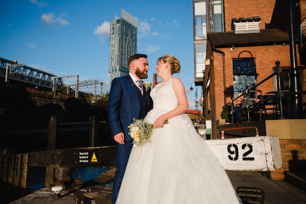 bride and groom at Lock 92 of Castlefield Rooms with Beetham Tower in background